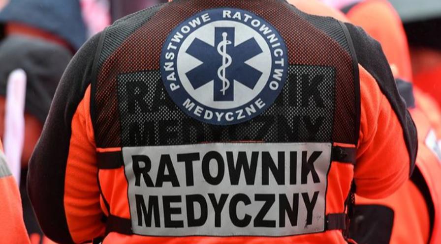 Mężczyzna odwrócony tyłem w ubraniu pomarańczowo czarnym z napisem na plecach ratownik medyczny.